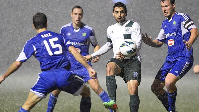 Hakoah players swarm a Northern Tigers player in torrential rain at Hensley Athletic Field.